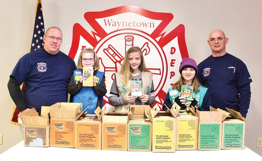 Waynetown Volunteer Firefighter Ryan Clevinger, left, and Fire Chief Phil Pirtle, right, stand with their Girl Scout partners Saturday before delivering $500 of Girl Scout cookies purchased by the department to elderly residents. Scouts riding along in the fire truck were Maiah Rathburn, from left, Lacie Bush and Elizabeth Ellingwood of Troop 57078 out of Crawfordsville.