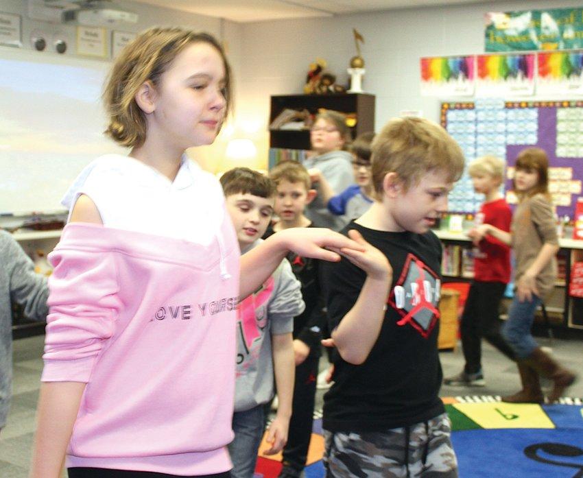 Ladoga Elementary fourth graders Kahlan Smith, left, and Josh Elliot learn a folk-style dance in Jennifer Ellingwood's music class on Thursday.