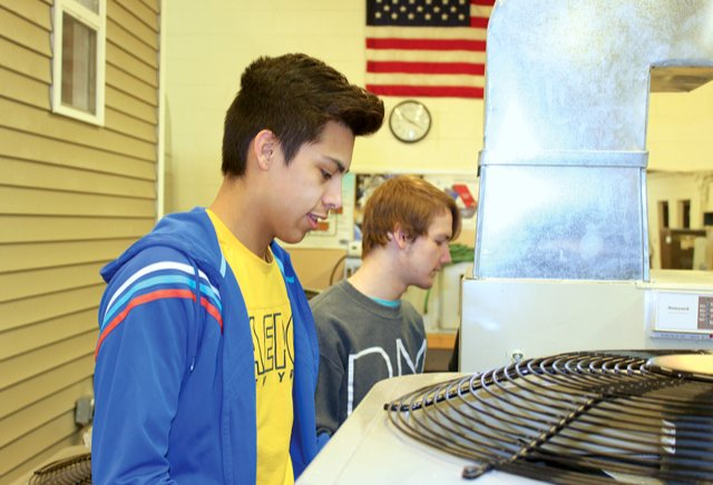 HVAC students James Tinoco, left, and Alex Brown prepare to move an air conditioning unit Friday at Crawfordsville High School.