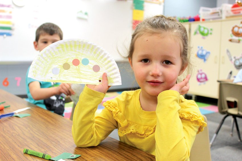 "Preschool student Carley Meseraull shows off her dinosaur Thursday. Asked if it was a stegosaurus, she replied, ""No. It's a dinosaur."""