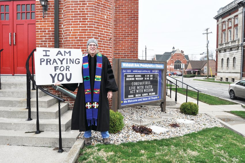 Rev. John Van Nuys, pastor of Wabash Avenue Presbyterian Church, holds a sign offering prayers Friday. The congregation has joined other local churches in suspending in-person worship services during the coronavirus (COVID-19) pandemic.