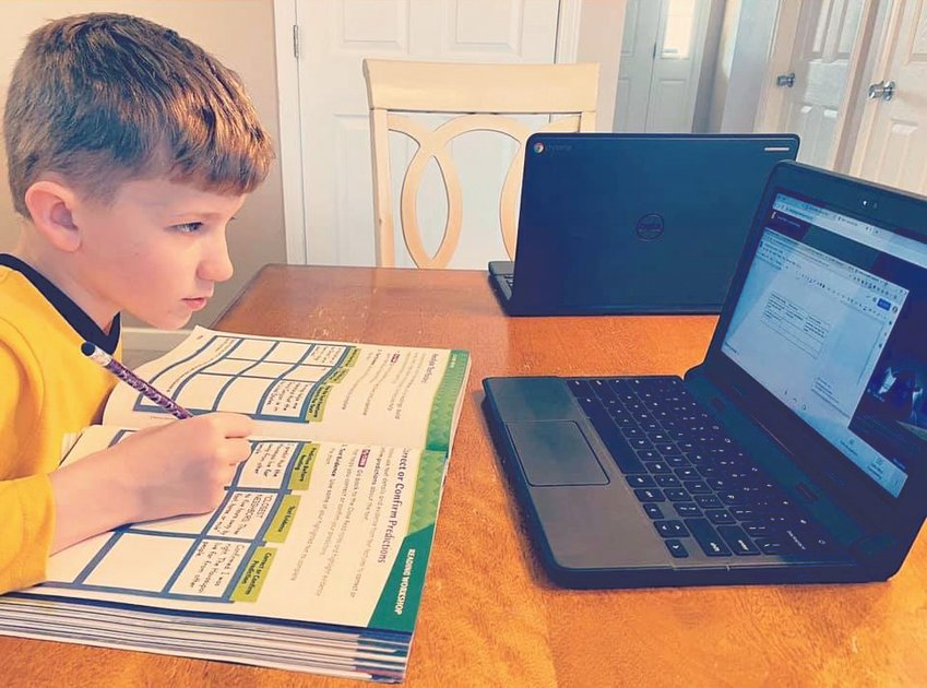 A New Market student does a math lesson while live video chatting with his teacher for help.