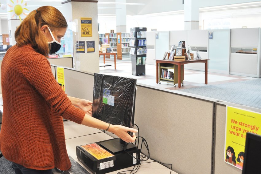 Megan Noggle adjusts a computer monitor after wrapping it with a plastic covering Wednesday at the Crawfordsville District Public Library. The library, which reopened Monday, strongly urges patrons to wear a mask and requires employees to cover their faces in public areas of the building.