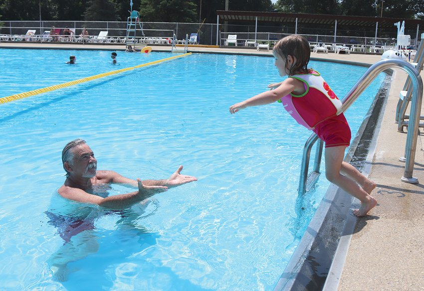 Rosalie Gleeson, 3, leaps into the Milligan Park Pool on Thursday while her father, Tim, waits to catch her.