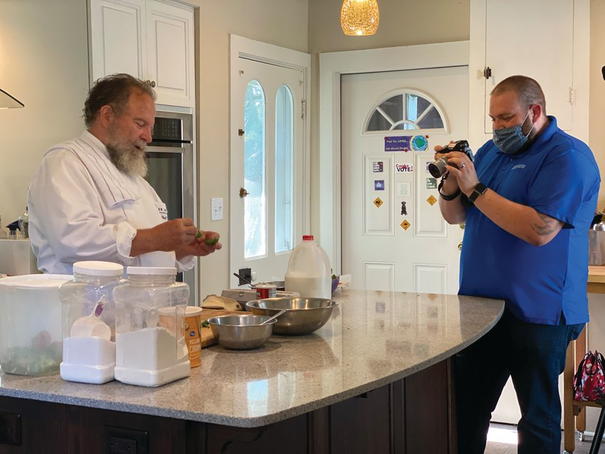 """Dr. Richard Warner prepares a recipe as Chuck Ranspach films the scene. Warner is featured in the Dr. Mary Ludwig Montgomery County Free Clinic's """"Dining with the Chefs: At Home Edition"""" on Aug. 8."""