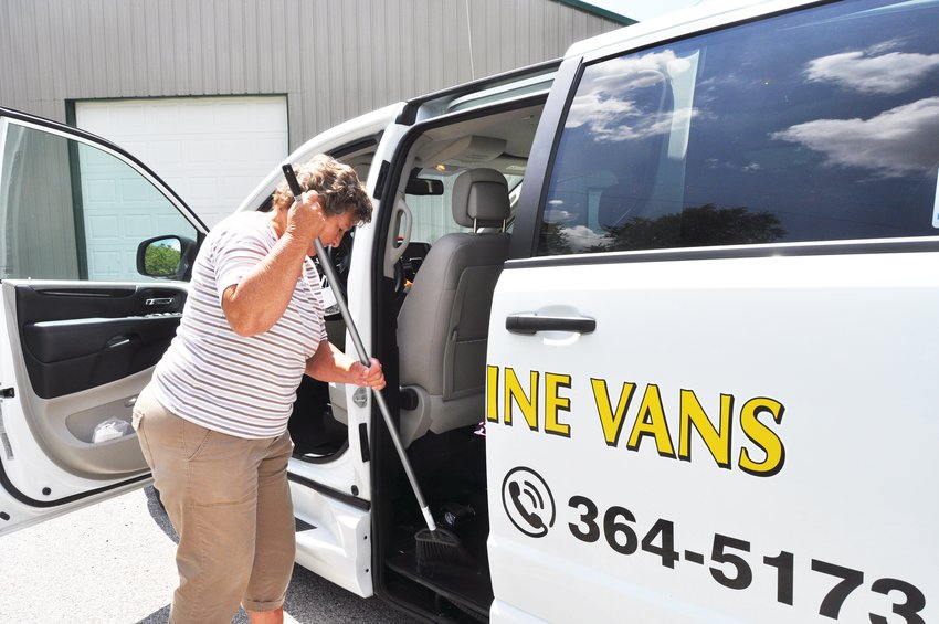 Roben Epps, lead driver for the Sunshine Vans program, sweeps out a van Friday in Milligan Park. The program is adding two new vans to its fleet through state and federal funding.
