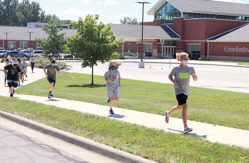 Henry Hartnett and Stormy Earls, front, head into the 20-second running portion of a couple warmup laps around the Crawfordsville Middle School parking lot Tuesday during physical education class.