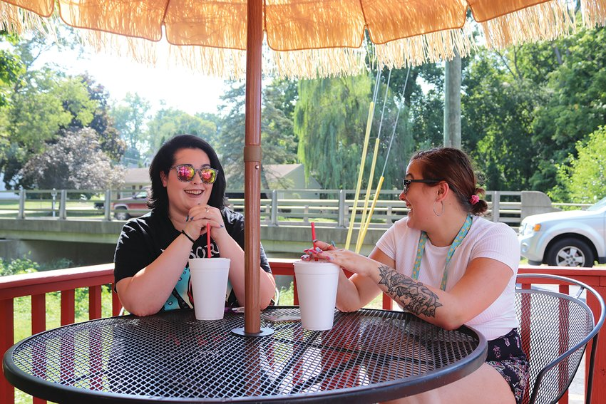 Brianna Melvin, left, and Haleah Maddox enjoy drinks in the shade Monday at The Big Dipper.