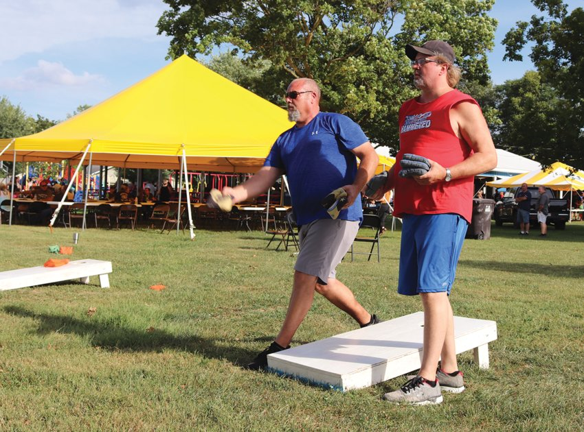 Rich Mesaros, left, and Larry McKinsey take turns throwing Saturday during a cornhole tournament at the Darren Forman Fundraiser in Waynetown. The event at Tremaine Park was created to benefit Montgomery County Coroner and Crawfordsville firefighter Darren Forman, who was seriously injured in July.