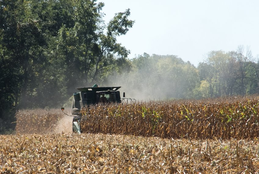 A farmer harvests his corn field near County Road 150 South.