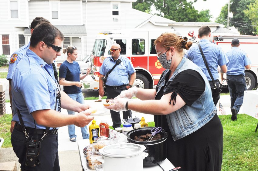Praise Sharp serves a hamburger to Crawfordsville firefighter/EMT Cody Haslam Saturday at The Pentecostals of Crawfordsville. The church served free food to first responders and military personnel to recognize the 19th anniversary of the Sept. 11 attacks.