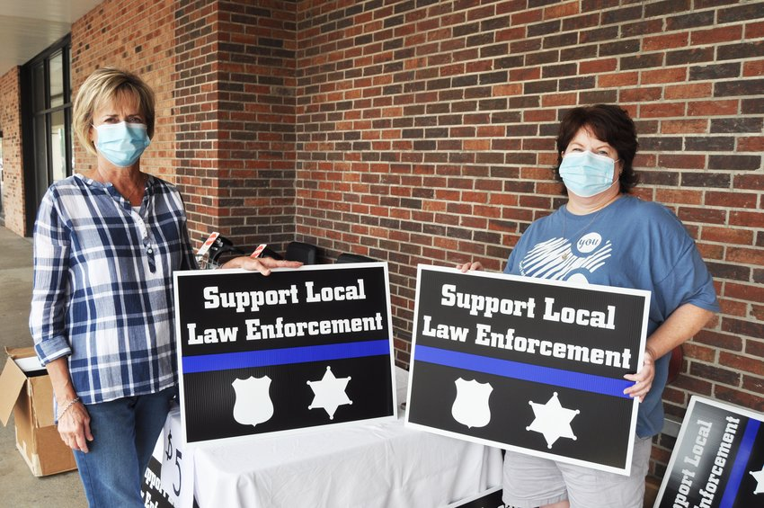Bonnie Mills, left, and Mindy Byers hold signs they were selling supporting local police officers Saturday at Kroger. The project has received support from surrounding counties.