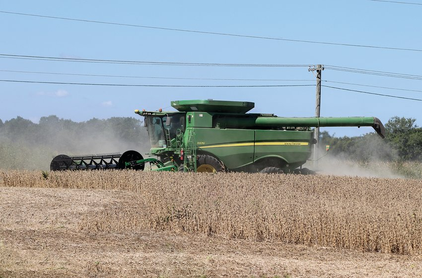 A farmer operates a combine in a field on C.R. 150S west of Crawfordsville High School.