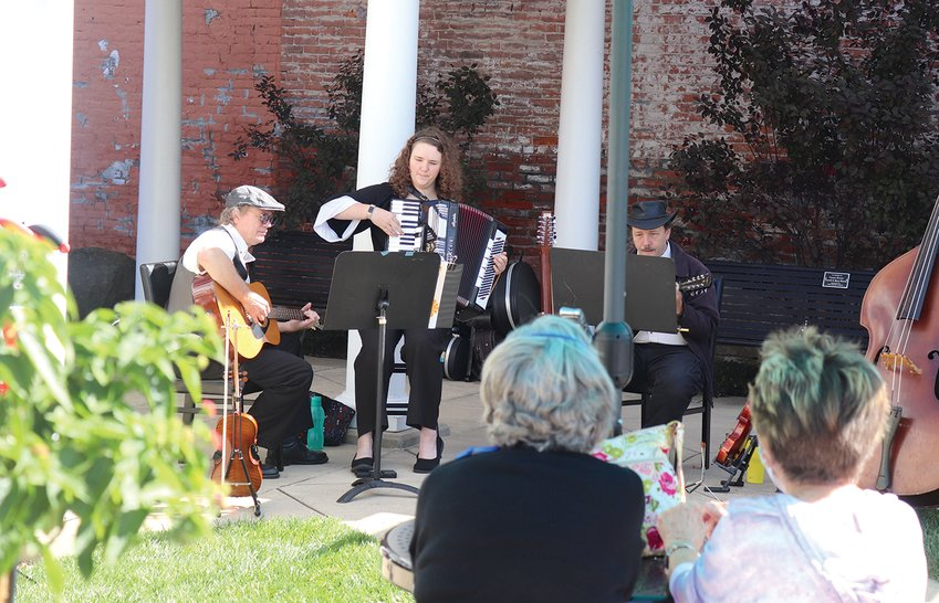 A local musical group called the Bal-Hinch Bunch performs Friday for patrons of Lunch on the Plaza event at the Marie Canine Plaza. A trio of the group's evolving membership were present for Friday's lunch, including Clayton Peters, from left, Josie Beach and Dennis Beach.