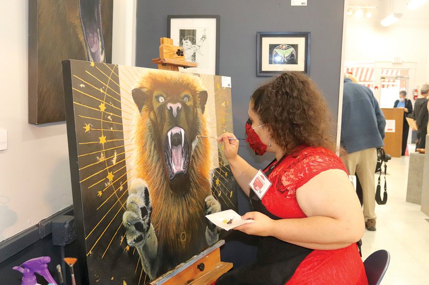 Athens Arts Gallery member artist Kenya Ferrand-Ott paints a manticore Sunday during an open house and fundraiser for the studio.