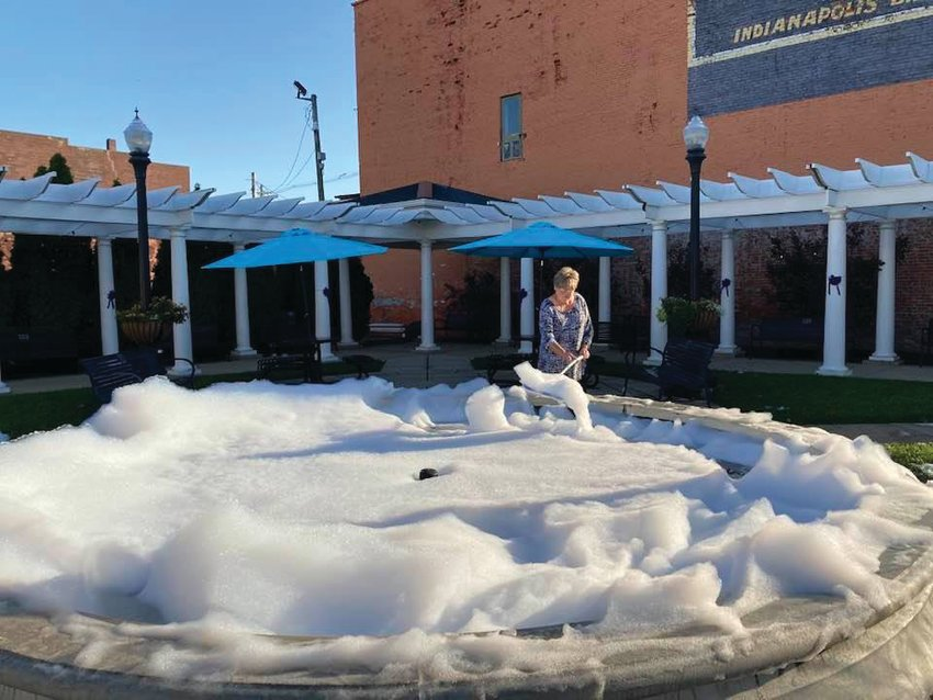 Sue Lucas, Crawfordsville Main Street program manager, scrapes foam out of the fountain at Marie Canine Plaza Friday. The fountain was soaped in the wee hours of the morning in an act of vandalism.