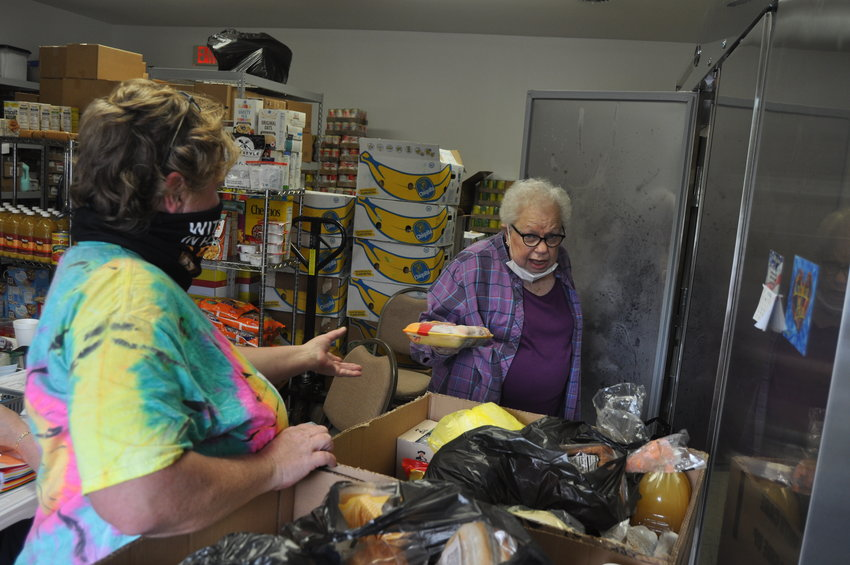 FISH Food Pantry manager Carol Spencer, right, hands a package of frozen chicken to volunteer Ellen Simpson on Friday. Area food pantries continue seeing high demand as the coronavirus pandemic wears on.