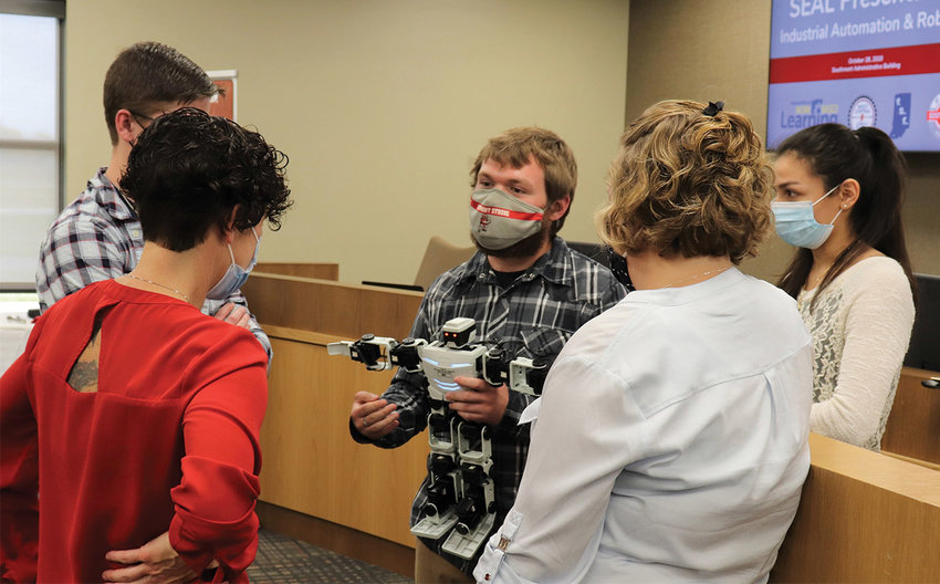 """Southmont's Cole Endicott, center, and fellow students Clayton Moellers and Rose Perez explain the process of using an """"ERIC"""" robot to Pace Dairy employee and Chamber President Tracy Mobley while course instructor Nicole Webb listens in."""