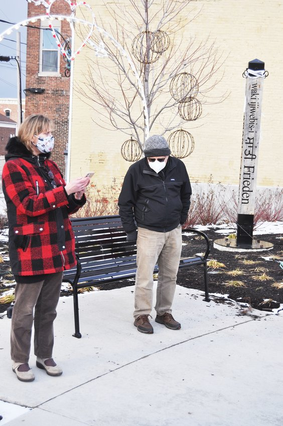 Kay Nannet, left, reads a tribute to Martin Luther King Jr. at Pike Place Monday.  A small group of members from Voices of Peace gathered at the Peace Pole to read quotes and sing