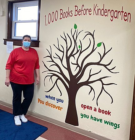 Bunny Sutton poses with the mural she created for the children's area of the Linden Public Library.