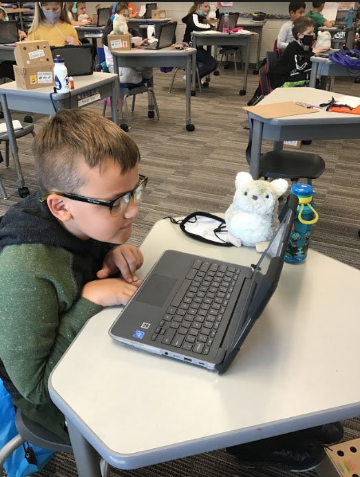 A Sugar Creek Elementary third grader uses a laptop computer with his Purrble nearby. The battery-powered stuffed animals are designed to help calm students.