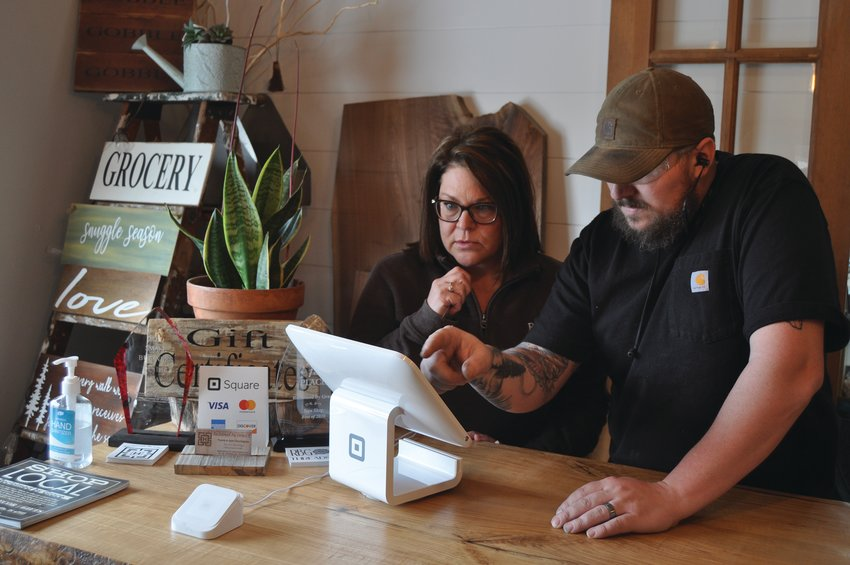 Travis Harrington, right, and Jami Harrington, owners of Reclaimed by Grace, use a Square device at the store Tuesday. Fusion 54 is seeking funding for an entrepreneur program and small business development and support.
