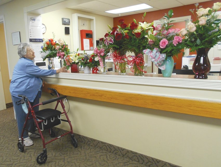 Irene Bratton, a resident of Hickory Creek at Crawfordsville, admires a special surprise flower delivery from Just Because Flower Shop. Bratton selected an arrangement for her room. Sherry Bratcher, Hickory Creek activities director, said the random act of kindness displayed by the local floral shop brightened the residents