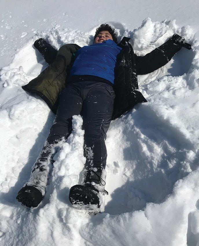 Randy and Lisa Deneau with Deigo make a snow angel.