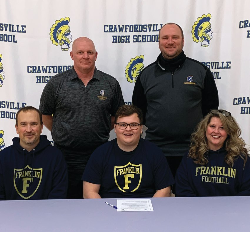 Crawfordsville senior football lineman Corbin Smith has committed to play at Franklin College. PICTURED: Corbin is joined by his parents, Scott and Michelle Smith, Crawfordsville head football coach Kurt Schlicher and assistant coach Sean Gerold.