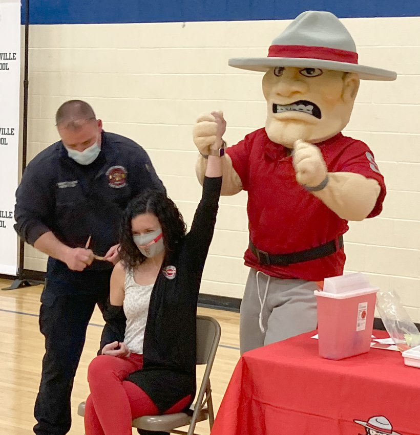 Samantha Cotten, Southmont communications coordinator and college and career readiness coach,  celebrates with the Mountie Man as community paramedic Spencer Stevens finishes administering her COVID-19 vaccine Monday at Crawfordsville High School.