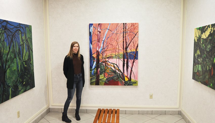 Caitlyn Brandt stands next to her paintings on display at Crawfordsville District Public Library