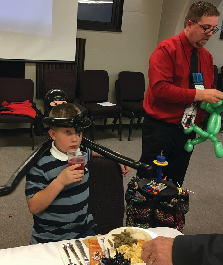 Aiden enjoys balloons made by the magician.