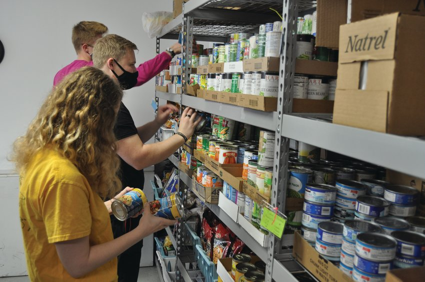 Leah Sizemore (holding the canned food), Elder Davis and Elder Jacobs, missionaries from The Church of Jesus Christ of Latter-day Saints, stock canned goods at the FISH Food Pantry Wednesday. The pantry has launched a delivery service for eligible elderly clients.
