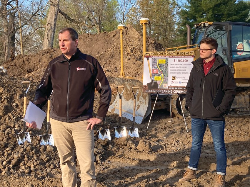 Jon Clodfelter, left, United Consulting bridge department manager, speaks at a groundbreaking ceremony for the C.R. 100W bridge replacement and roadway realignment project as bridge design engineer Bradley Salpietro looks on Friday at the construction site.