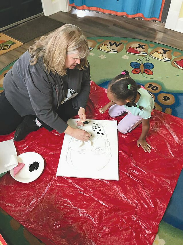 Stacy Bogan works with a student.