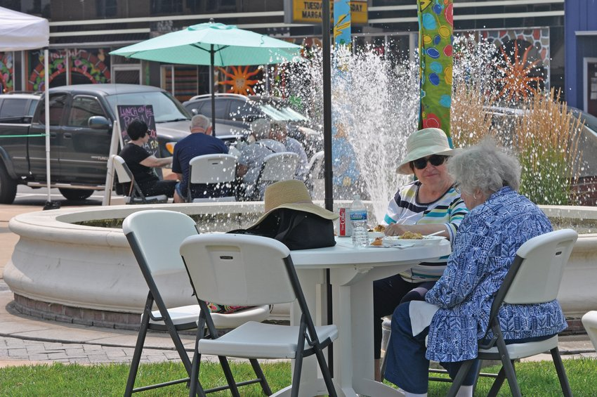 Two women eat at Marie Canine Plaza during Crawfordsville Main Street