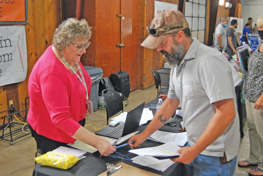 Bonnie Mann, director of human relations for Penguin Random House, hands a pen to Dan Busenbark, who gathered information on job opportunities Thursday at the Crawfordsville/Montgomery County Job Fair at the Montgomery County Fairgrounds.