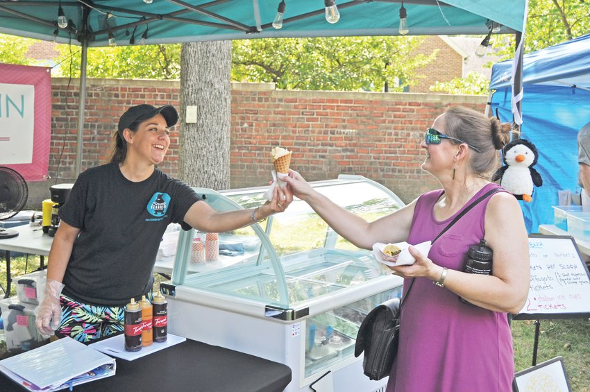 Julie Simpkins, left, of Street Penguin Gelato serves a cone to Karen Gunther at the Taste of Montgomery County on the grounds of the General Lew Wallace Study & Museum on Saturday.