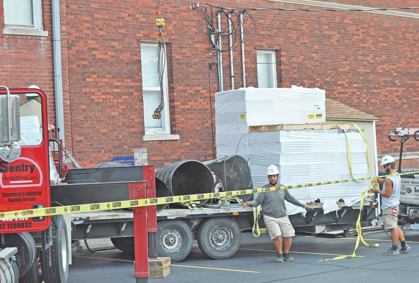 Workers from Sentry Roofing prepare to hoist supplies onto the roof of the Masonic Cornerstone Grand Hall & Event Center on Monday. The crews were beginning the process of replacing the roof of the historic downtown structure.