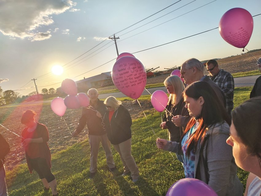 Chelsy Lawrence, second from right, holds a balloon at a celebration of life ceremony for her brother, Travis Lawrence, on the first anniversary of his death in May.
