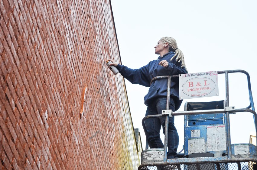 Jenna Morello paints a mural in the alley between the Montgomery County Community Foundation and Milligan's Flowers and Gifts on Monday. The mural will feature various wildflowers native to Indiana.