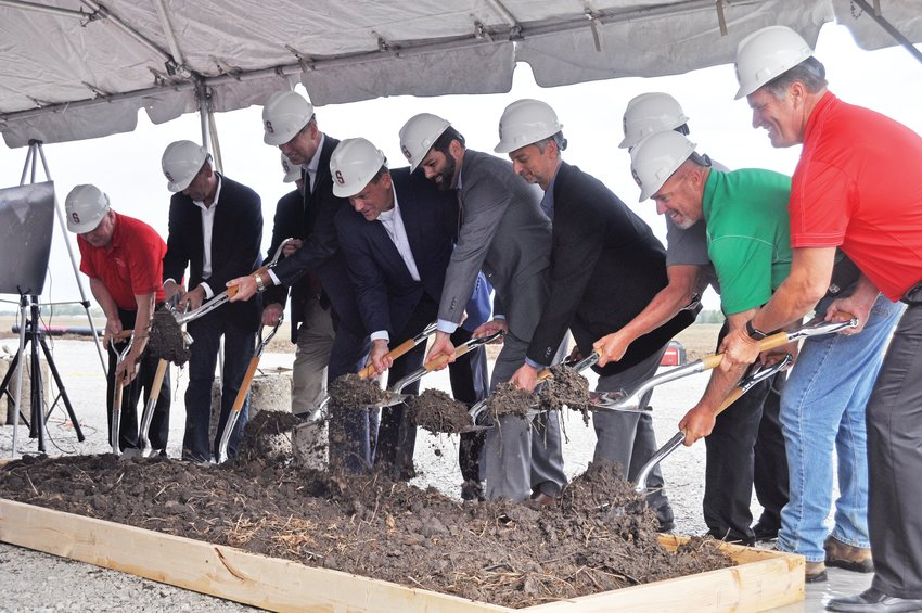 Dignitaries turn dirt at a groundbreaking ceremony for the Tempur Sealy plant on Thursday.