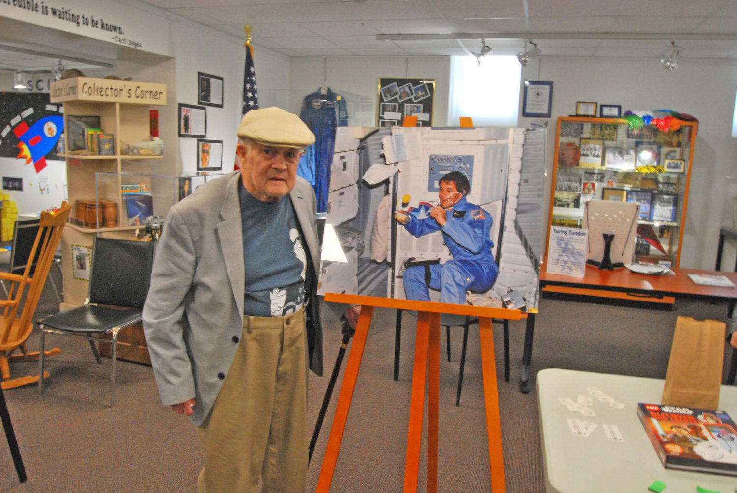 Retired astronaut Joe Allen stands next to a photo of himself from a 1980s space shuttle flight at the Carnegie Museum of Montgomery County. Allen visited the museum to help celebrate the 50th anniversary of the moon landing.