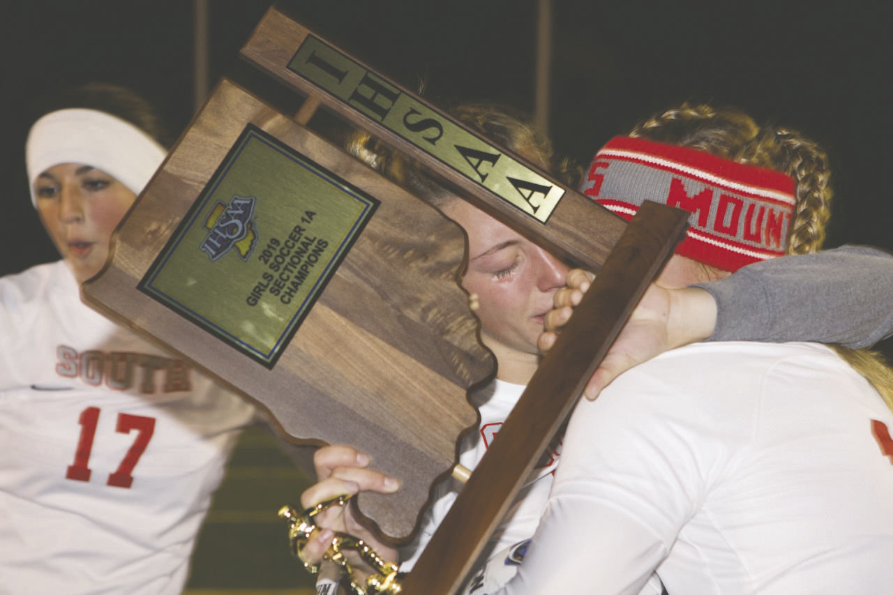 Senior Lexie Odum sheds tears of joy as she clings to the sectional championship trophy and a teammate following Southmont's 1-0 sectional title win over North Putnam.