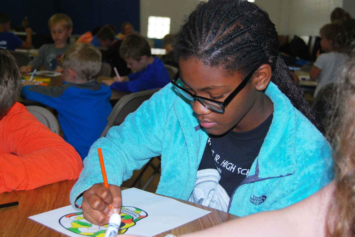 Shaahia Burks, 14, colors a picture Monday at the Boys & Girls Club of Montgomery County. Themed events for the camp include S.T.E.M., a picnic, Kid Olympics and a costume party.