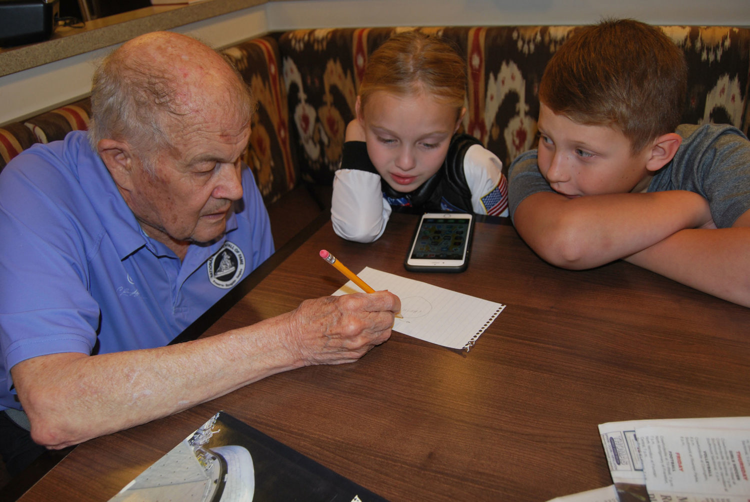 Retired NASA astronaut Joe Allen, left, explains gravity to Anniston Miles and Sebastian Kochert Tuesday. Anniston, a second-grader, wants to be an astronaut.