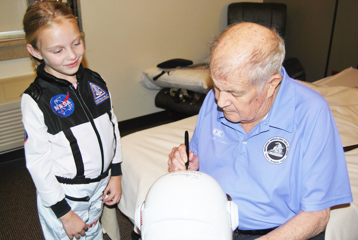 Retired NASA astronaut Joe Allen signs the helmet of Anniston Miles' astronaut costume Tuesday. Anniston plans to dress up as an astronaut for Halloween.