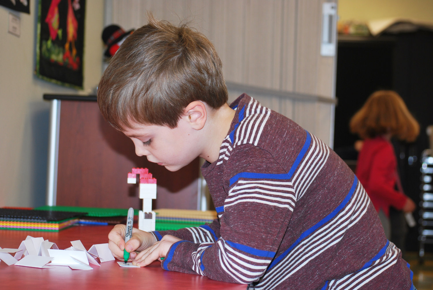 Jamie Wilson signing his name on his Snowman for the lego challenge