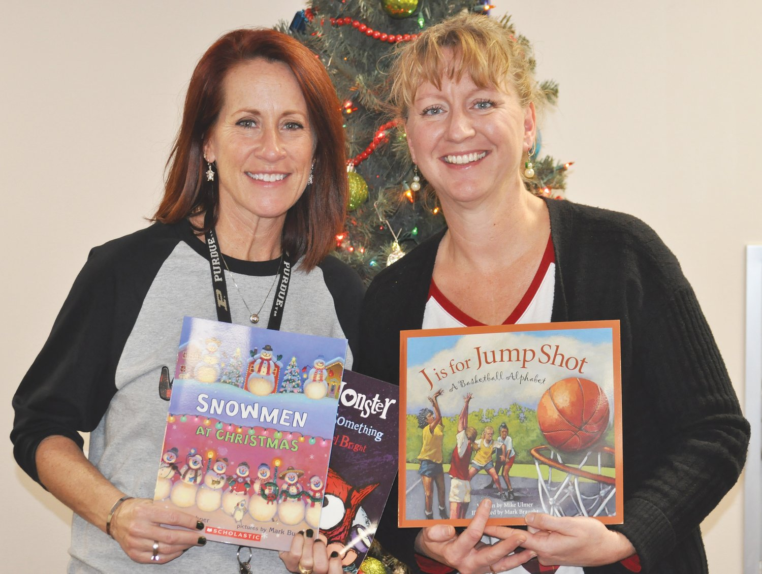 Amber Rohr, left, and Amy Hensley hold some of the books they were able to purchase with the help of a grant.