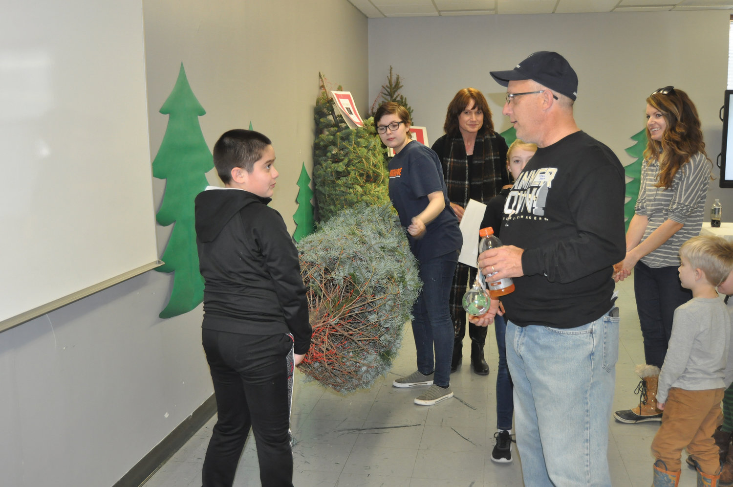 Northridge Middle School sixth grader Moises Berumen-Correa, left, speaks with veteran Darrell Borth as classmate Cambria Hall waits to carry a Christmas tree to Borth's car. The trees were donated to local servicemember families through the school's Project Evergreen. Also pictured are social studies teacher Jodi Webster and Oak Hill Tree Farm co-owner Rachel Stine, whose business grew the trees.